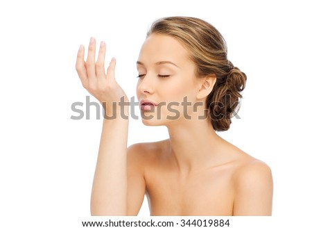 beauty, aroma, people and body care concept - young woman smelling perfume from wrist of her hand - stock photo