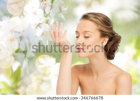 beauty, aroma, people and body care concept - young woman smelling perfume from wrist of her hand over green natural background with cherry blossoms - stock photo