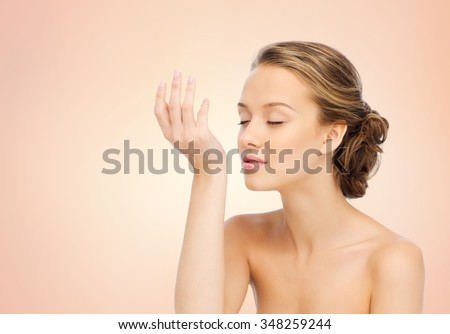 beauty, aroma, people and body care concept - young woman smelling perfume from wrist of her hand over beige background - stock photo