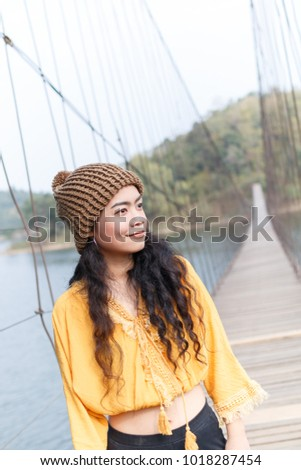 beauty asian woman in yellow wear and black jeans and wool hat on the wooden bridge