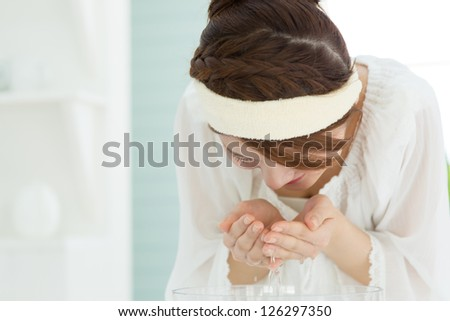 Beauty asian woman washing her face with clean water - stock photo