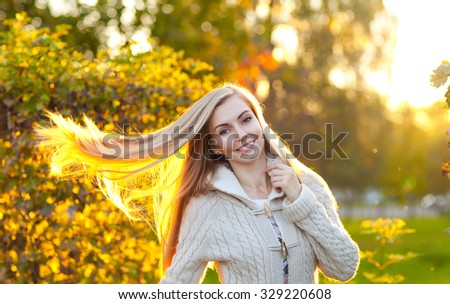 Beauty attractive young woman with long blonde hair joy in the park