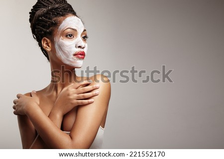 beauty black woman with a facial mask - stock photo