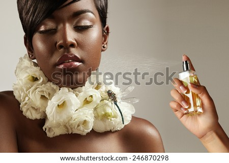beauty black woman with flowers on her neck and a hand with a perfume bottle - stock photo