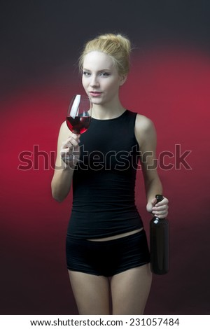 beauty blond model holding wineglass with red wine and wine bottle getting ready to take sip  - stock photo
