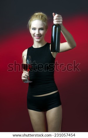beauty blond model holding wineglass with red wine and wine bottle saying Cheers with gesture  - stock photo