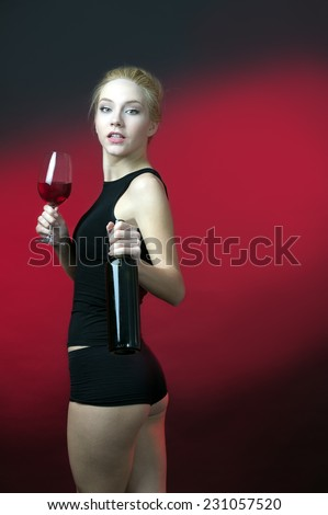 beauty blond model holding wineglass with red wine and wine bottle turn her torso at back side  - stock photo