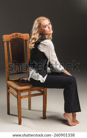 Beauty blond woman  in a black suit and white shirt, sitting on a chair on a gray background - stock photo