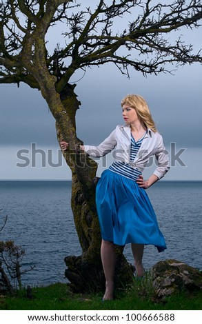 beauty blond woman stand on sea coast - stock photo