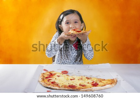 Beauty blonde dressed in black and white sweater spotted eating a pizza on a yellow background  - stock photo
