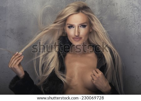 Beauty blonde woman in black fur