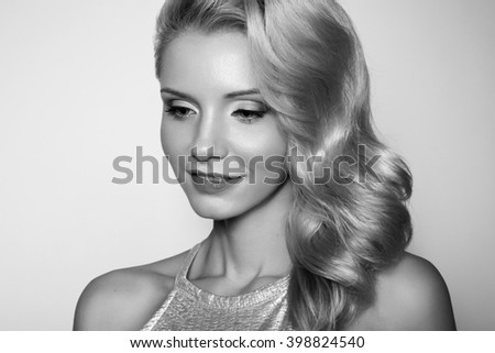 Beauty Blonde Woman Portrait. Beautiful model girl with curly blond hair. Hairdressing, hairstyle. Sexy Model. Perfect Skin and Make up. Black and white photo.