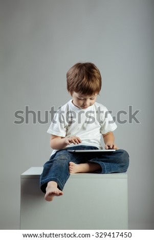 beauty boy with tablet PC - stock photo