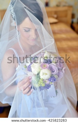 Beauty bride in dressing gown with bouquet and lace veil indoors. Beautiful model girl in colorful wedding robe. Female portrait of cute lady. Woman with hairstyle