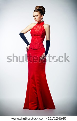 Beauty bride in long bridal red dress and black gloves - studio shot. Formal party - stock photo