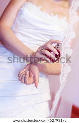 Beauty bride spraying perfume on her wrist.