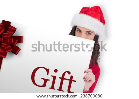 Beauty brunette in santa hat showing gift card against white background with vignette - stock photo