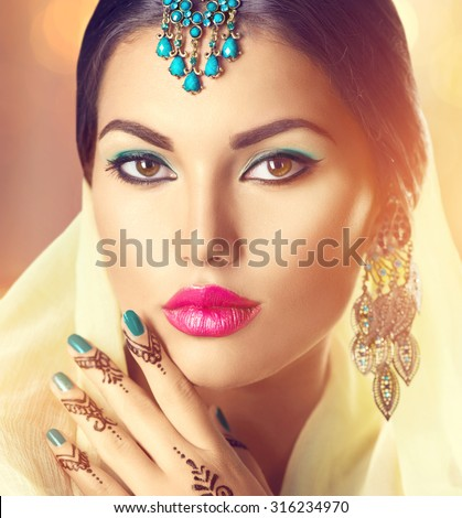 Beauty brunette Indian woman portrait. Hindu model girl with brown eyes, mehndi tattoo on hand and national Indian jewels looking in camera. Indian girl in sari. Marriage Traditions. Indian culture - stock photo