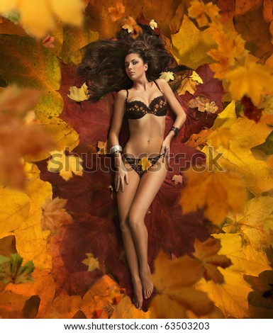 Beauty brunette laying on the leaves carpet - stock photo