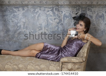 Beauty brunette model sitting on antique couch, bites chocolate bar  - stock photo