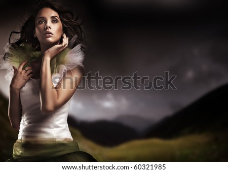 Beauty brunette posing over dark sky background - stock photo