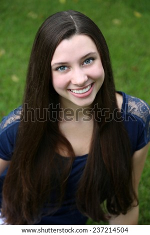 beauty brunette teen girl with big eyes sitting in grass - stock photo