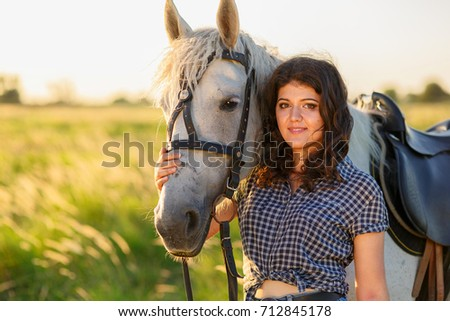 beauty brunette woman with horse in field