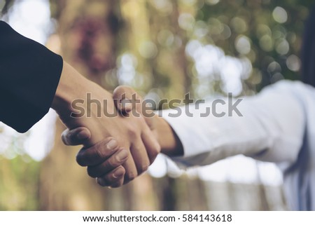Beauty Business partnership meeting concept. Image business people handshake. Successful businesswomen handshaking after good deal.Blurred background.Split tone instragram like process.
