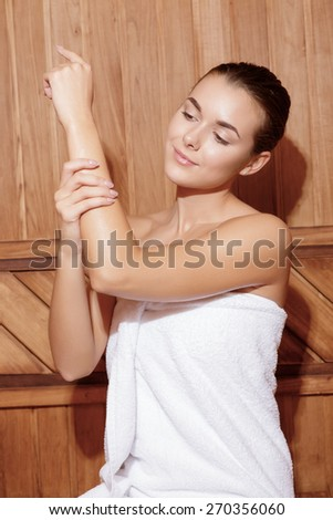 Beauty care. Vertical shot of a young joyful woman caring after her skin in wooden sauna room - stock photo