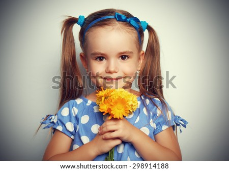 Beauty child girl in a blue dress with a bouquet of yellow flowers - stock photo