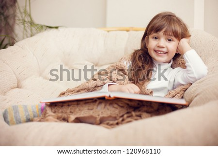 beauty child in shawl reading a book while lying on the couch. - stock photo