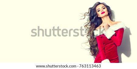 Beauty Christmas fashion model girl, wearing red santa dress. Sexy brunette young woman with long curly hair. Stylish female, fashionable party clothes and accessories, makeup and hairstyle