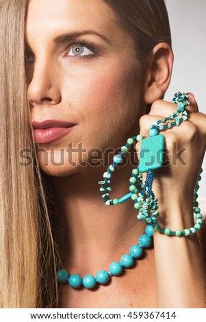 Beauty close up face head young woman necklace hand long hair side view