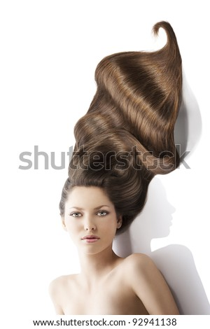 beauty close-up portrait of beautiful female face with long dark waved hairs laying down on the white. she looks in to the lens with searius expression. - stock photo