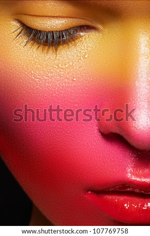 Beauty close-up portrait of beautiful woman model face with magic creative fashion multicolored make-up. Face painting, cosmetics, beauty and makeup.