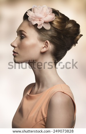 beauty close-up portrait of very pretty young woman posing turned on profile with elegant hair-style, flower on the head and linear simple orange dress  - stock photo