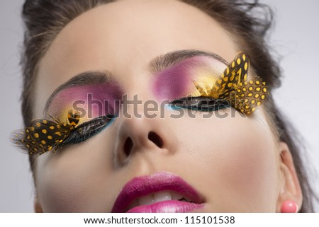 beauty close-up portrait with colored and feathered make up, she looks down at left - stock photo