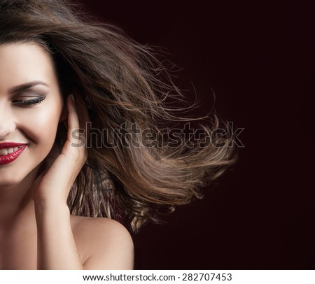 Beauty closeup portrait of attractive elegant brunette woman with red lips and long hair. Perfect makeup. Wind in hair.Girl with toothy smile.