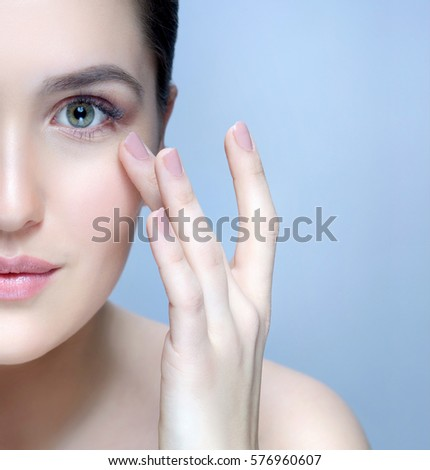 beauty closeup portrait of attractive young  caucasian woman brunette on blue background studio shot lips face skin care applying cream head and shoulders looking at camera hands