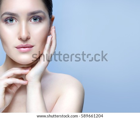 beauty closeup portrait of attractive young  caucasian woman on blue background studio shot lips face skin care hands near the face looking at camera spa . Touching her fresh perfect skin. copy space