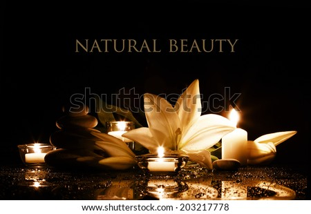 beauty composition with white lily, burning candles and stack of stones in gold and black colors  - stock photo