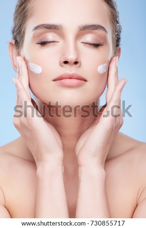 Beauty concept, beauty portrait of young woman applying cream on face with closed eyes, anface. Head and shoulders of naturally beautiful woman touching face, studio, inside
