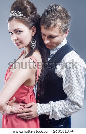 Beauty Concept: Caucasian Handsome Man Embracing Beautiful Caucasian Brunette with Tiara Crown. Over Gray Background.Vertical Image Orientation - stock photo