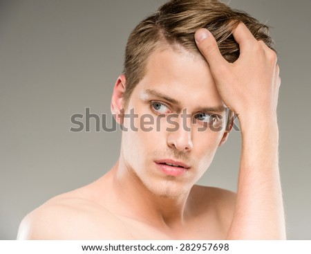 Beauty concept. Handsome man with naked torso looking away. - stock photo