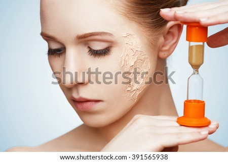 beauty concept rejuvenation, renewal, skin care and skin problems with hourglass - stock photo