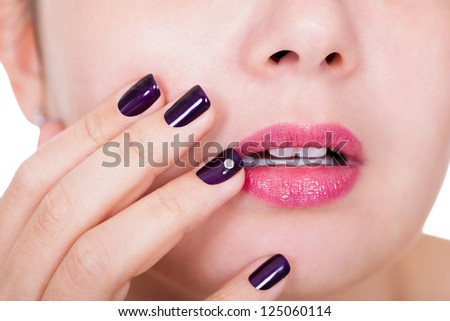 Beauty concept with a woman holding her manicured beautiful purple nails against her glossy pink slightly parted lips - stock photo