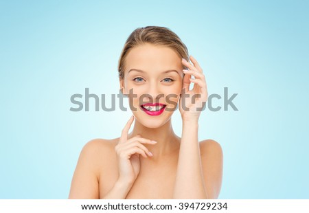 beauty, cosmetics, people and health concept - smiling young woman with pink lipstick on lips touching her face over blue background - stock photo