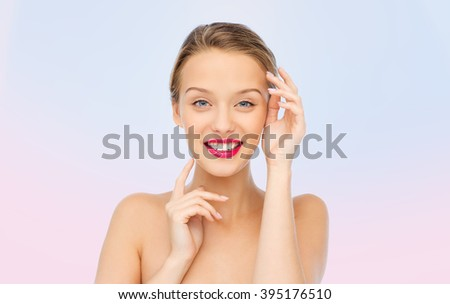 beauty, cosmetics, people and health concept - smiling young woman with pink lipstick on lips touching her face over rose quartz and serenity gradient background - stock photo