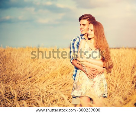 Beauty Couple relaxing on wheat field together. Happy girlfriend and boyfriend having fun outdoors, kissing and hugging, first love concept. Beautiful Boy and Girl in love together - stock photo