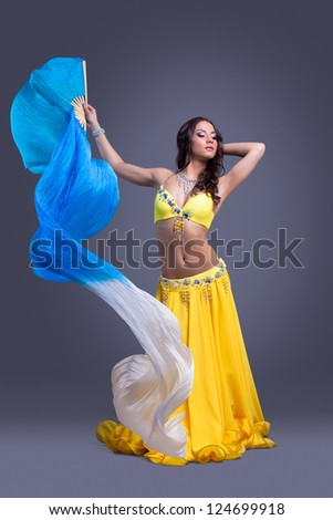 Beauty dancer in yellow costume dance with fantail - stock photo